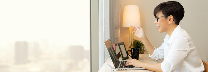 Beautiful and smart looking Asian businesswoman video call with computer laptop from home during...
