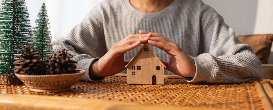 Closeup image of a woman protecting and covering wooden house model by hands with warmness