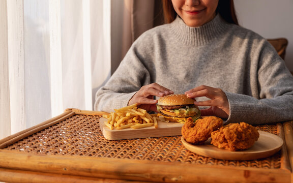 Closeup image of a young asian woman holding and eating hamburger and french fries with fried chicken on the table at home