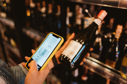 Woman customer scanning barcode from wine bottle label using smart phone