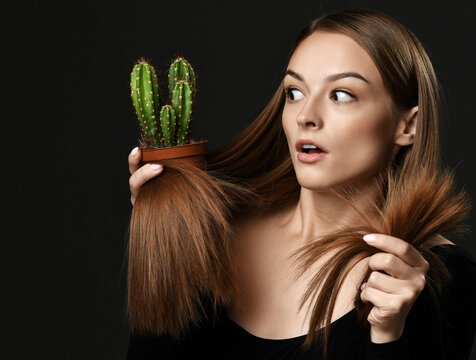 Frustrated shocked young woman in black clothes with long silky straight hair compares hair split ends with cactus plant in pot she holds over dark background. Haircare, beauty, wellness concept