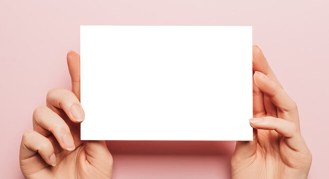Female hands hold a blank sheet of paper on a pink background. Advertising space