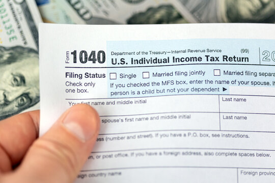 Man hand holding US individual income 1040 tax form under dollar bills