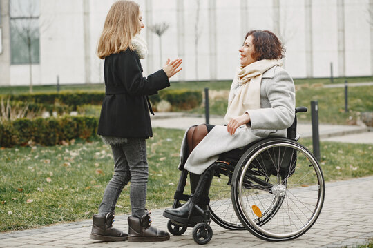 Disabled woman in wheelchair with daughter. Family walking outside at park.