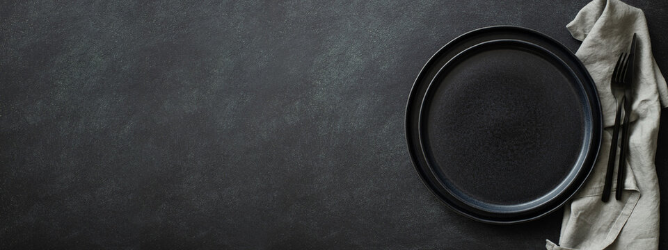 Empty black plates with black cutlery and gray napkin on black table. Top view, banner for website.