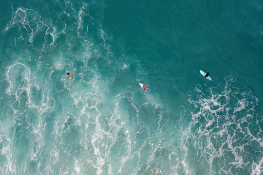 Aerial photograph of the ocean with crashed waves and surfers