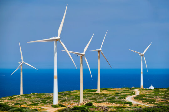 Green renewable alternative energy concept - wind generator turbines generating electricity. Wind farm on Crete island, Greece with small white church
