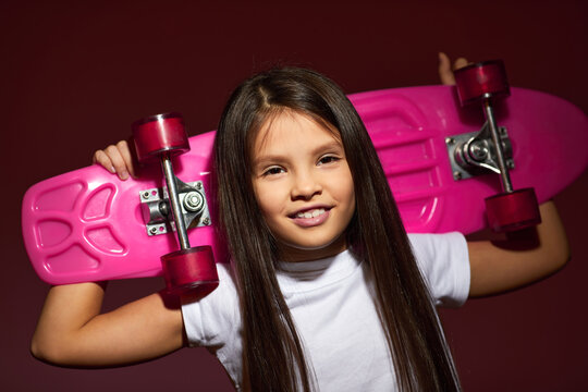 portrait of little child girl holding pink skateboard on studio background.