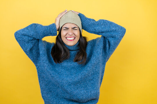 Young beautiful woman wearing blue casual sweater and wool hat suffering from headache desperate and stressed because pain and migraine with her hands on head