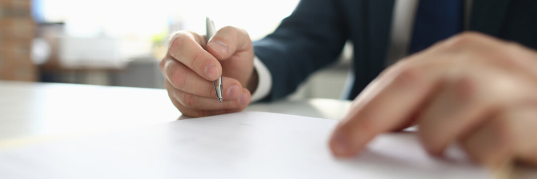 Close-up of smart businessman sitting in luxury office. Clever clerk signing agreement. Well-dressed suit. White working table. Business and development in career concept