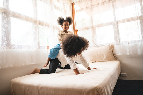 Two African American siblings girls jumping on sofa bed while having fun at home