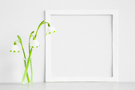 Fresh snowdrops in glass vase on table at light gray blue wall. First messengers of spring. Empty place for inspirational, emotional, sentimental text, quote or sayings in white frame. Closeup.