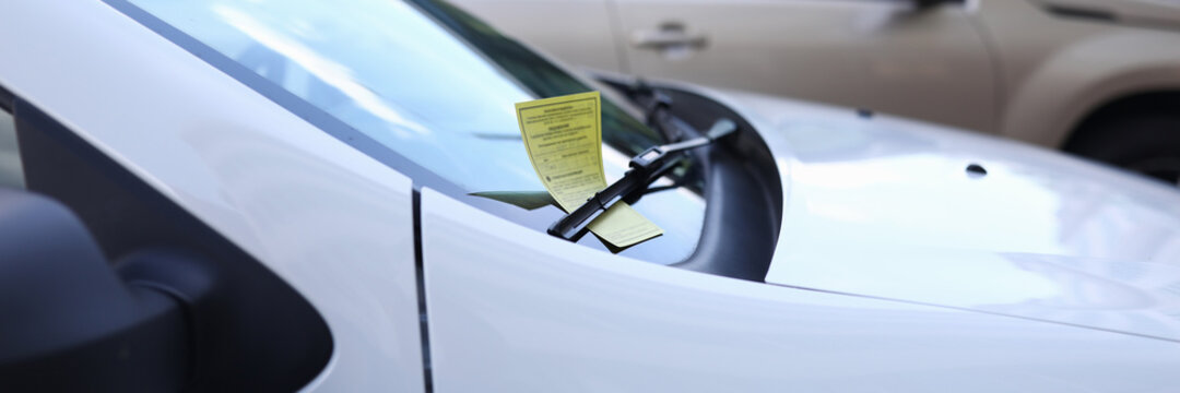 Close-up of white automobile with parking ticket under windshield wiper. Auto on street. Penalty charge notice paper. Luxury vehicle. Illegal and law concept
