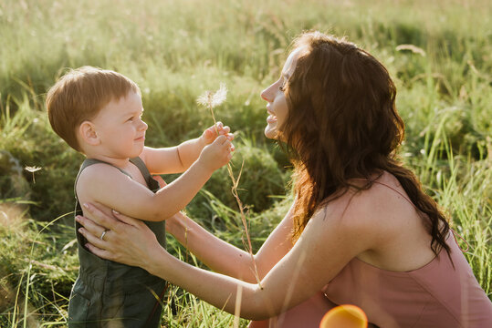 Little boy and mom are holding a dandelion in their hands on the field.
