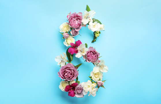 Number 8 made of beautiful flowers on light blue background, flat lay. International Women's day