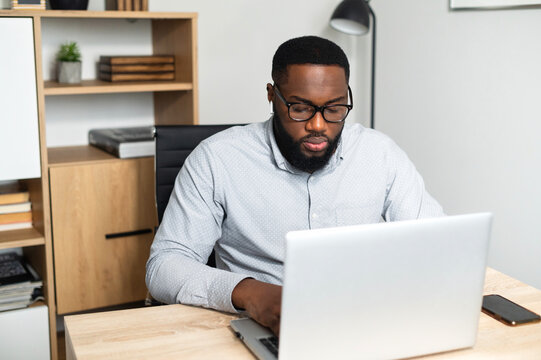 Concentrated young African-American male office worker in glasses sitting at the desk and typing on a laptop, participating in the online conference. A student stressing, taking an online exam