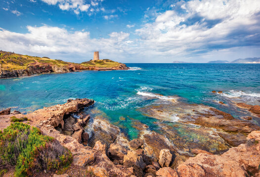 Beautiful marine scenery. Splendid morning view of Piscinni bay with Torre di Pixinni tower on background. Sunny summer scene of Sardinia island, Italy. Gorgeous Mediterranean seascape.