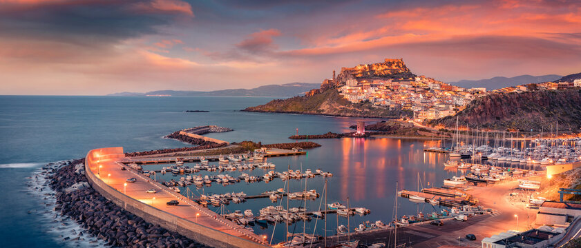 Сharm of the ancient cities of Europe. Panoramic evening cityscape of Castelsardo port. Stunning sunset on Sardinia island, Province of Sassari, Italy, Europe. Mediterranean seascape.