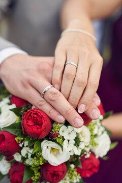 Hände eines Brautppaares mit Eheringen über Brautstrauß