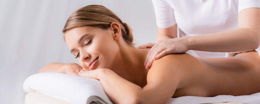 masseur massaging pleased client lying on massage table, banner