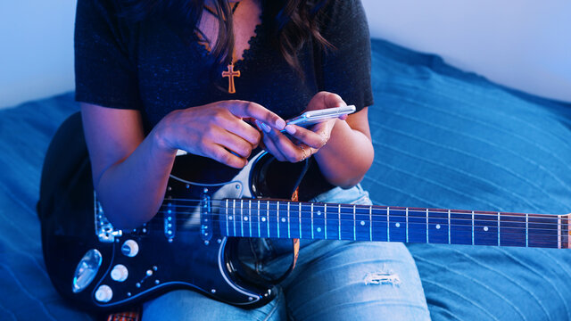 Young woman musician holding acoustic guitar while using smartphone. Close up. High quality photo