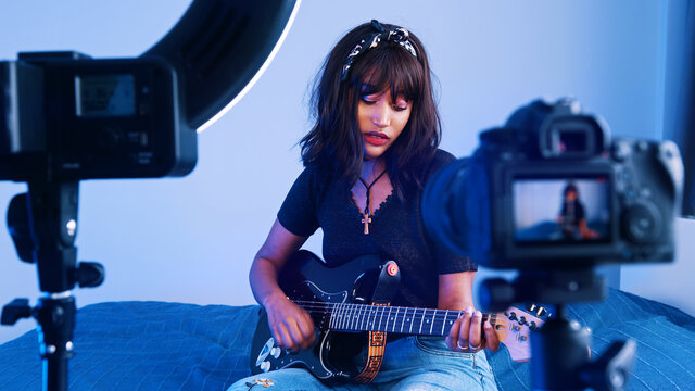 Young woman playing guitar in front of the camera. recording demo or giving online class. High quality photo
