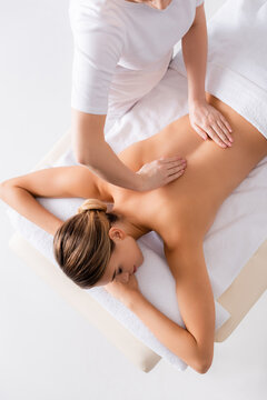 high angle view of masseur massaging back of young woman on massage table