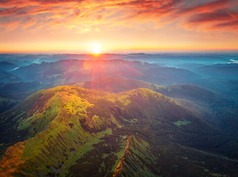 Beautiful summer scenery. First sunlights glowing mountain hills and valleys. Astonishing summer scene of Carpathian mountains , Ukraine, Europe. Beauty of nature concept background.