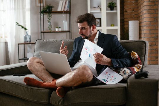 Young man working online, wearing suit and no pants. Young man having video call. Businessman working at home..