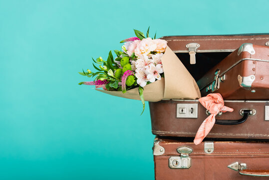 bouquet of fresh flowers and vintage suitcases isolated on turquoise