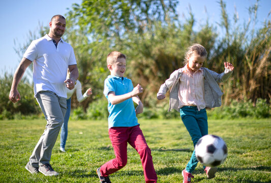 family with children playing soccer on the grass in the park
