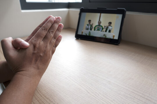 A man is praying with hands in praying position while watching a mass is live streamed with a tablet at home when all Catholic churches are closed because of covid-19 pandemic