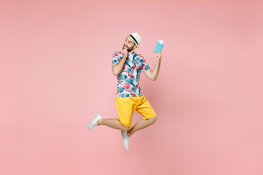 Full length pensive traveler man in summer clothes hat jumping hold passport tickets put hand prop up on chin isolated on pink background. Passenger traveling on weekend. Air flight journey concept.