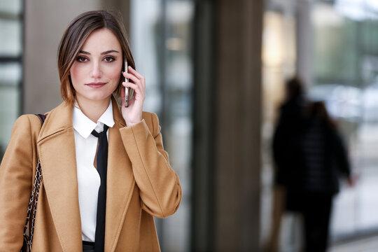 manager donna con cappotto beige , camicia bianca e cravatta nera cammina in contesto urbano utilizzando il suo smartphone