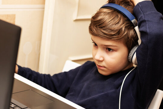 Little boy homeschooling and e-learning over laptop at home.