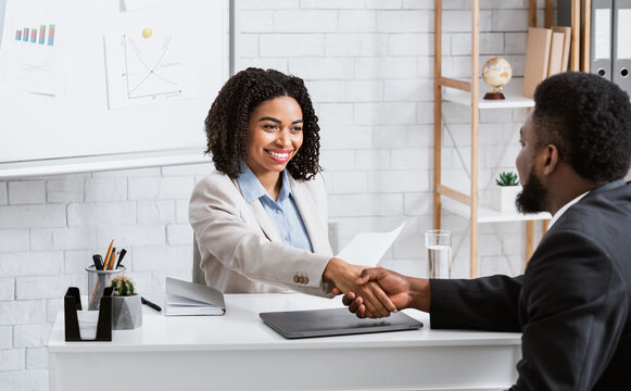 Positive female personnel manager and black job applicant shaking hands before employment interview at company office