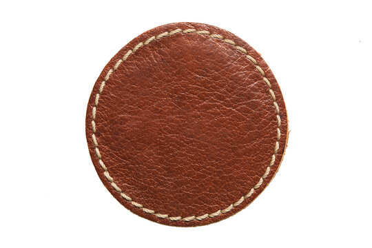 Blank brown round leather label on white background, macro close up. Empty leatherette circular tag