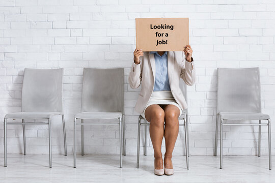Young African American woman covering face with LOOKING FOR JOB sign while waiting for employment interview at office