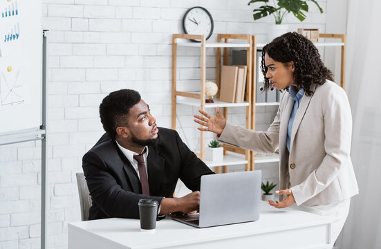 Angry African American lady boss scolding male employee for error in urgent project at office. Workplace stress concept