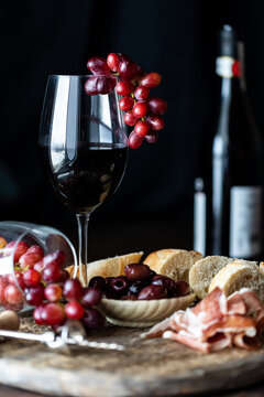 A wine glass with red grapes hanging over the rim against a dark background on a rustic charcuterie board.