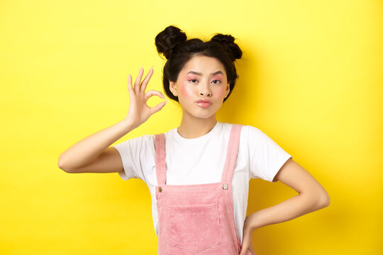 Sassy teenage asian girl with bright pink makeup, showing okay sign and nod in approval, approve product with serious face, not bad gesture, standing against yellow background