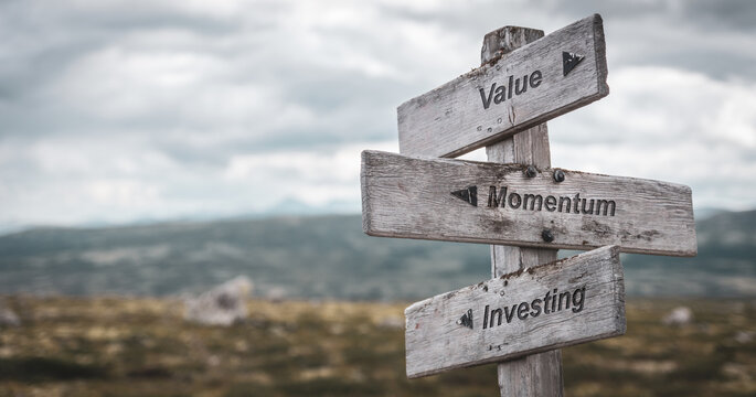 value momentum investing text engraved on wooden signpost outdoors in nature. Panorama format