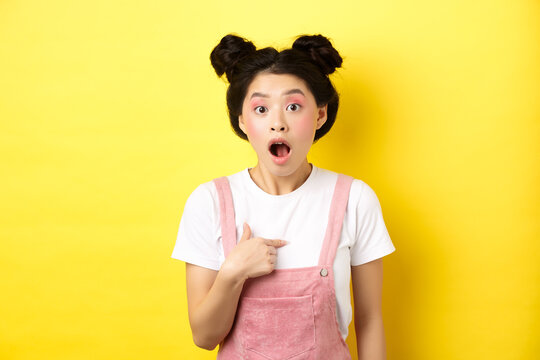 Surprised asian teen girl with glamour makeup, pointing at herself and gasping confused, being chosen or accused, standing on pink background