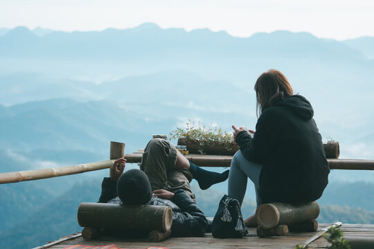 Happy couple lying on terrace coffee shop while resting on top of a mountain.