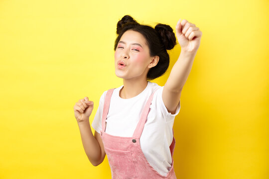 Excited asian girl looking motivated, raising hand up and chanting, cheering with joy, standing happy on yellow background
