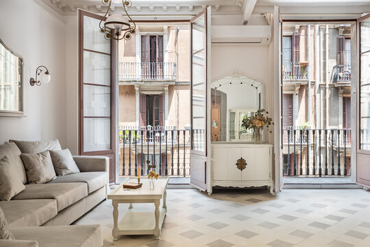 Front view to the vintage style living room with sofa, tile floor, retro lamps and balconies. Refurbished apartment in Barcelona old city