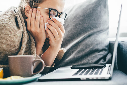 Woman blowing nose, holding handkerchief, sneezing during working with laptop in living room at home.