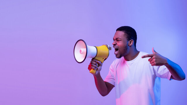Full length portrait of aggressive young man shouting using megaphone isolated over purple studio wall, copyspace