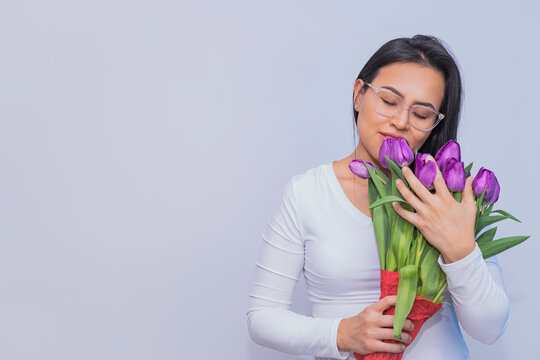 Mujer Latina sosteniendo un ramo de tulipanes.