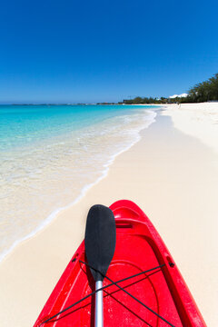 Colorful red kayaks with paddles on a tropical beach on summer day.  Seven Mile Beach, Grand Cayman, Cayman Island, Caribbean